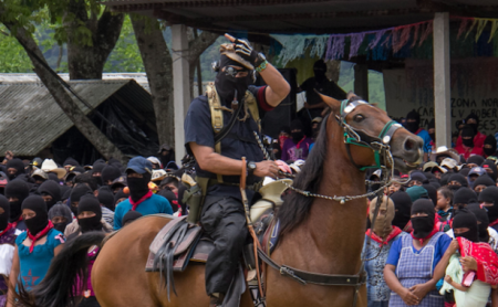 The man formerly known as Subcomandante Marcos arrives in the main square of La Realidad before issuing his final communique. In his greeting to the crowd, he raised a middle finger to the audience — one of the multiple tricks and jokes that he played on the crowd throughout the ceremony. (WNV/Marta Molina)