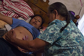 "Dona Mercedes, a traditional midwife, checks on Maria Lopez Mendoza, then six months pregnant, shortly before she declared Lopez's baby ""una nina"" - a girl."
