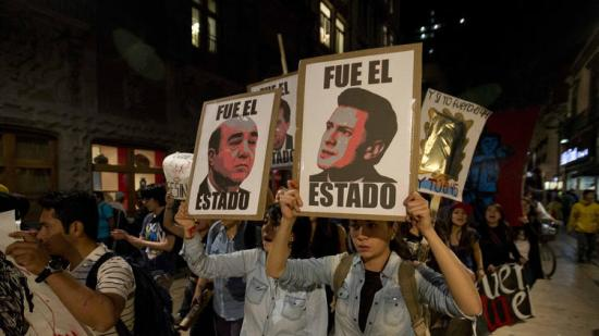 """In Mexico City, demonstrators march with signs saying """"It was the state"""" and showing images of Mexican President Enrique Peña Nieto, right, and Atty. Gen. Jesus Murillo Karam in a protest over the disappearance of 43 college students. (Eduardo Verdugo / Associated Press)"""