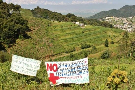 """Partial view of the Otomi-Mexica Forest which is critical for the preservation of the aquifer as well as native traditions. Photo by Daniel Vargas, Más de 131. (Translation left sign: """"Here we breathe struggle, the sub-reality of living in a community with no more identity; right sign: No repression, no devastation, no intimidation, no freeway."""")"""