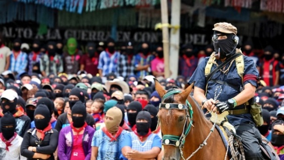 Subcomandante Marcos rides horseback in front of the Zapatista support base members in La Realidad during an homage to fallen compañero Galeano, who was killed in a paramilitary attack on May 2, 2014. | Photo: Tim Russo/Upside Down World